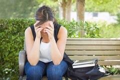 Frustrierte junge Frau, die allein auf Bank nahe bei Büchern sitzt Stockbild