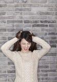 Frustrierte junge Frau, die ihr Haar zieht Stockfotos