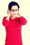 Frustrierte junge Frau, die ihre Ohren anhält Lizenzfreie Stockfotografie