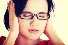 Frustrierte junge Frau, die ihre Ohren anhält Stockfotos