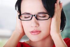 Frustrierte junge Frau, die ihre Ohren anhält Stockbild