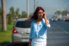 Frustrierte junge Frau, die Problem mit Auto hat lizenzfreies stockbild