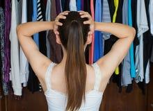 Frustrierte junge Frau kann was nicht entscheiden, von ihr nah zu tragen Stockfotos