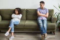 Frustrierte tausendjährige Paare sitzen auseinander auf der Couch, die nicht afte spricht lizenzfreie stockfotografie