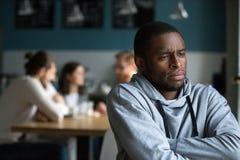 Frustrierter afrikanischer Mann leidet unter Rassendiskriminierung allein stockbild