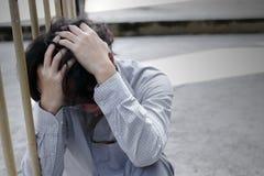 Frustrierter betonter junger asiatischer Geschäftsmann mit den Händen, die Kopf berühren und enttäuscht oder mit Job erschöpft gl Lizenzfreie Stockfotografie