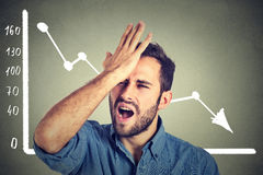 Frustrierter betonter junger Mann hoffnungslos mit der Finanzmarktdiagrammgraphik, die unten geht stockbild