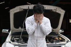 Frustrierter betonter junger Mechanikermann in der weißen Uniform, die sein Gesicht mit den Händen gegen Auto in der offenen Haub Stockfotografie