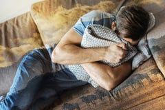 Frustrierter deprimierter Mann, der durch das Kissen liegt und sich versteckt Stockfotografie