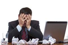Frustrierter desperated Mann, der am Schreibtisch sitzt lizenzfreies stockbild