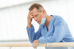 Frustrierter Doktor. Deprimierter reifer Doktor im blauen einheitlichen Stand Lizenzfreies Stockbild