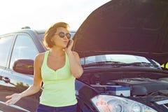 Frustrierter Frauenfahrer nahe defektem Auto Auto auf Landstraße, Frau nennt das Bitten um Hilfe lizenzfreie stockfotos