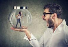 Frustrierter Geschäftsmann, der ein Glasgefäß mit einer verärgerten schreienden Frau eingeschlossen in ihm hält stockbild