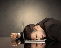Frustrierter Geschäftsmann ` s Kopf auf Tastatur Stockfoto