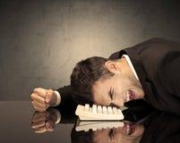 Frustrierter Geschäftsmann ` s Kopf auf Tastatur Lizenzfreie Stockbilder