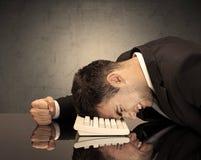 Frustrierter Geschäftsmann ` s Kopf auf Tastatur Stockfotos