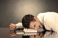 Frustrierter Geschäftsmann ` s Kopf auf Tastatur Lizenzfreies Stockfoto