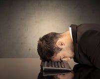 Frustrierter Geschäftsmann ` s Kopf auf Tastatur Stockbilder
