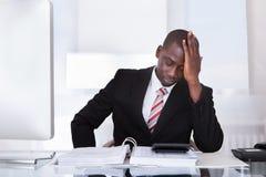 Frustrierter Geschäftsmann am Schreibtisch Stockbild