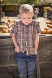 Frustrierter Junge am Kürbis-Flecken-Bauernhof, der gegen hölzernen Lastwagen steht Stockbilder