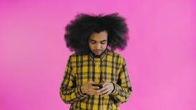 Frustrierter junger Afroamerikanermann, der defekten Handy auf purpurrotem Hintergrund hält Konzept von Gef?hlen stock footage