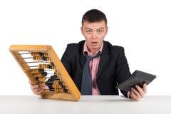 Frustrierter junger Geschäftsmann mit Taschenrechner und Abakus Stockfoto