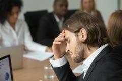 Frustrierter müder Geschäftsmann, der starke Kopfschmerzen an verschiedenem t hat stockfotografie