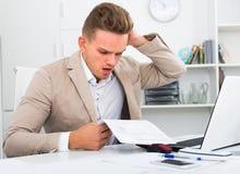 Frustrierter Manager, der Schreibarbeit im Büro tut Stockfotografie