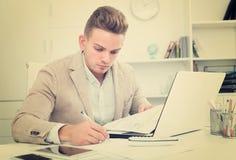 Frustrierter Manager, der Schreibarbeit im Büro tut Lizenzfreie Stockfotos