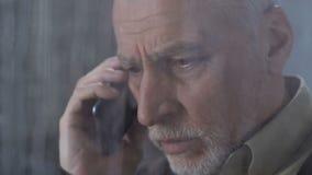 Frustrierter Mann, der schwer hören schlechte Nachrichten auf Smartphone am regnerischen Tag seufzt stock video footage