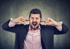 Frustrierter Mann, der seine Ohren mit den Fingern verstopft lizenzfreies stockfoto