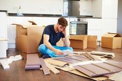 Frustrierter Mann, der Selbstbau-Möbel zusammenfügt Stockfotos