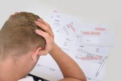 Frustrierter Mann mit unbezahlten Rechnungen Lizenzfreie Stockbilder
