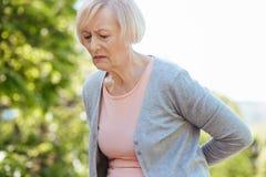 Frustrierter Pensionär, der draußen unter den Schmerz in der Rückseite leidet Lizenzfreies Stockfoto