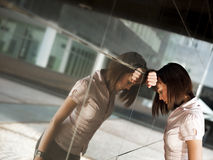 Frustrierter schlagender Kopf der Frau gegen Wand Stockbilder