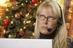 Frustrierter Telefon-Empfangsdamen-Using Laptop Wearing-Kopfhörer nahe Weihnachtsbaum Stockfoto