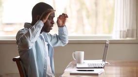Frustrierter umgekippter schwarzer Mann unter Verwendung der Laptopleseschlechten Nachrichten online stock video footage