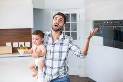 Frustrierter Vater, der schreiendes Baby in der Küche hält Stockfotografie