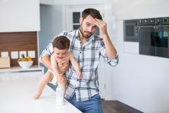 Frustrierter Vater, der schreiendes Baby hält Lizenzfreies Stockbild
