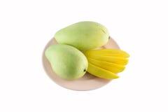 Fruta amarilla fresca del mango en el plato aislado en el fondo blanco Imágenes de archivo libres de regalías