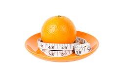 Fruta anaranjada con la cinta de la medida en la placa anaranjada Imagenes de archivo