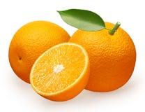 Fruta anaranjada con la hoja verde al lado de la mentira y a medias Imágenes de archivo libres de regalías