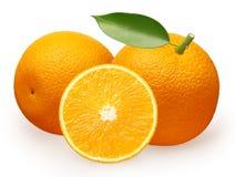 Fruta anaranjada con la hoja verde al lado de la mentira y a medias Imagen de archivo libre de regalías