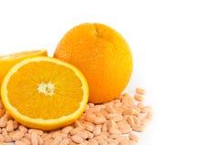 Fruta anaranjada con la tablilla de la vitamina C Foto de archivo libre de regalías
