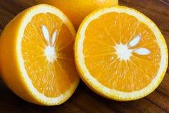 Fruta anaranjada cortada por la mitad Imagen de archivo libre de regalías