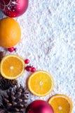 Fruta anaranjada de la Navidad con la especia del anís del canela y de estrella, el muérdago y el fondo de la nieve Imagen de archivo libre de regalías