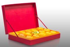Fruta anaranjada en caja roja Imágenes de archivo libres de regalías