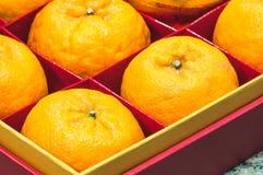 Fruta anaranjada en caja roja Imagenes de archivo