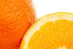 Fruta anaranjada entera y sus segmentos encendido Foto de archivo libre de regalías