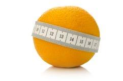 Fruta anaranjada envuelta con la cinta métrica Fotografía de archivo